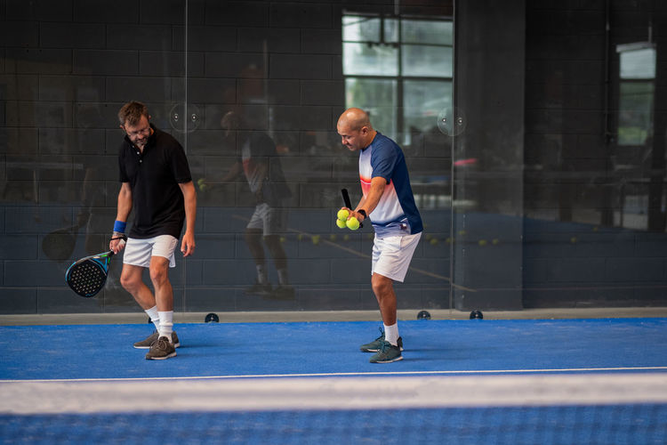 Monitor teaching padel class to man, his student - trainer teaches boy how to play padel