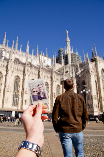 Woman Holding Photograph Of Couple By Church