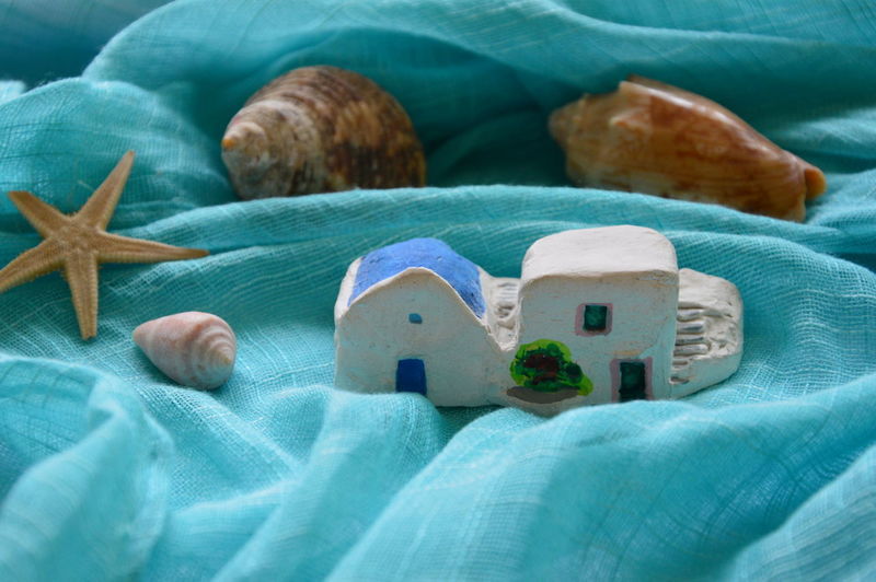 High Angle View Of House And Seashells On Turquoise Fabric