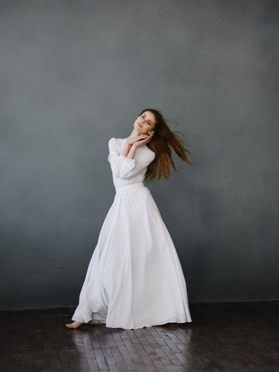 Woman looking away while standing against white wall