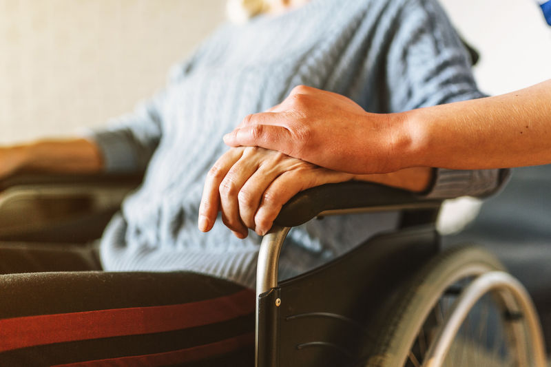 Cropped hand consoling woman sitting on wheelchair