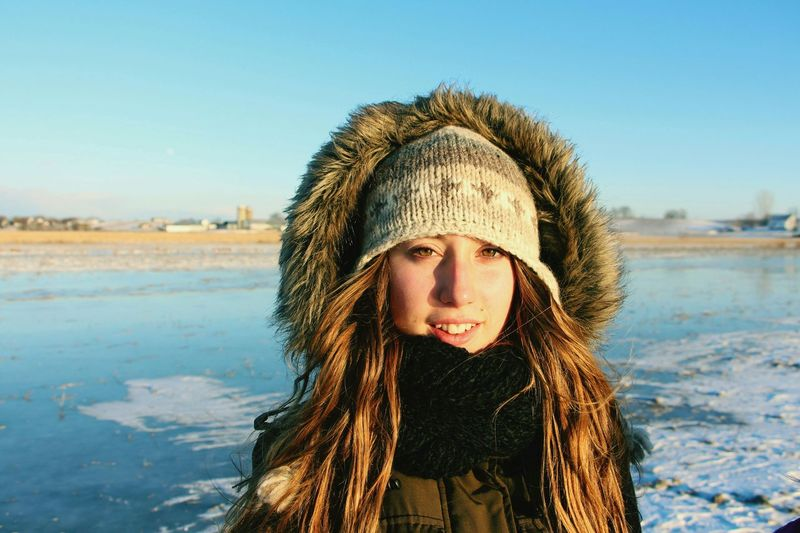Portrait Of Smiling Young Woman With Warm Clothing Against Sky