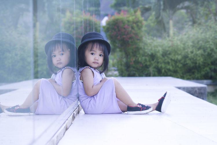 Portrait of girl sitting against glass