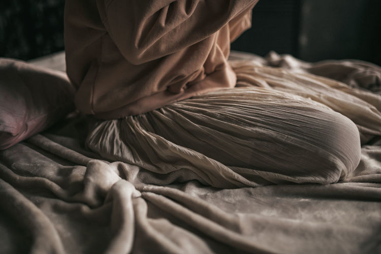 Close-up of hands working on bed