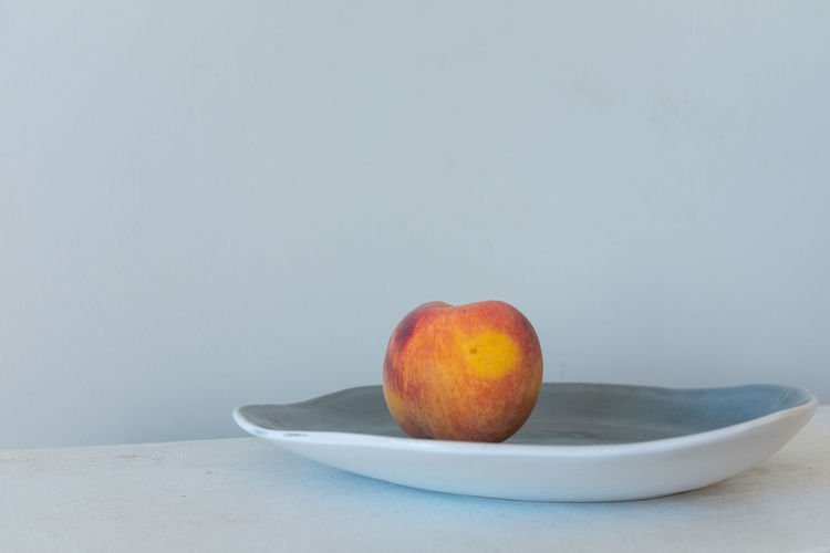Close-up of fruits in bowl on table against white background