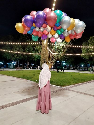 Rear view of woman with balloons standing on street