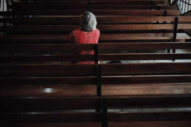 Rear View Of Woman Sitting On Pew At Church