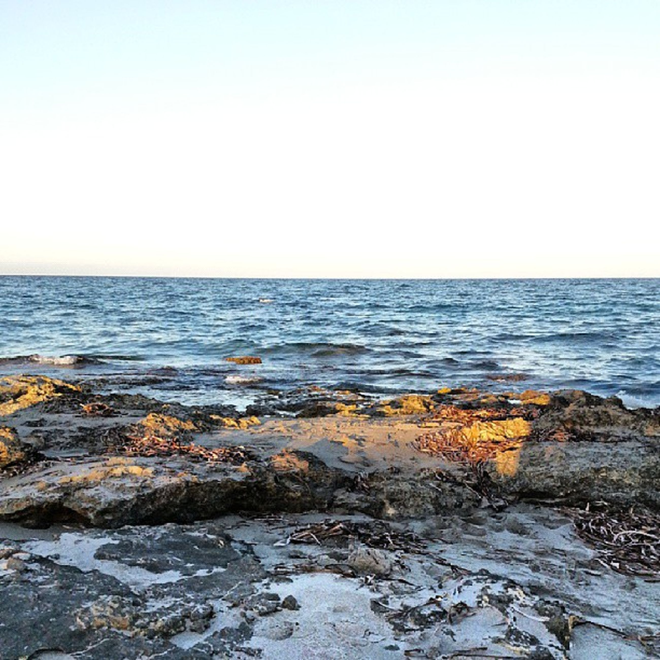 sea, water, horizon over water, clear sky, scenics, beauty in nature, tranquil scene, copy space, tranquility, rock - object, beach, nature, shore, wave, idyllic, remote, blue, rock formation, outdoors, non-urban scene