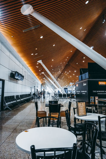 Modern Architecture Architectural Column Cafe Indoor Modern Airport Airportphotography Airport Terminal Chair Empty Ceiling Illuminated Architecture Moving Walkway  Airport Departure Area Tall - High Arrival Departure Board