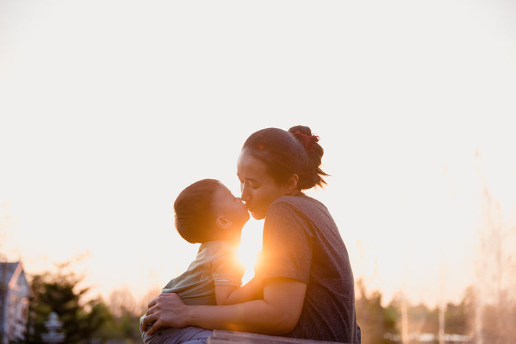 Mother and son kissing against sky during sunset
