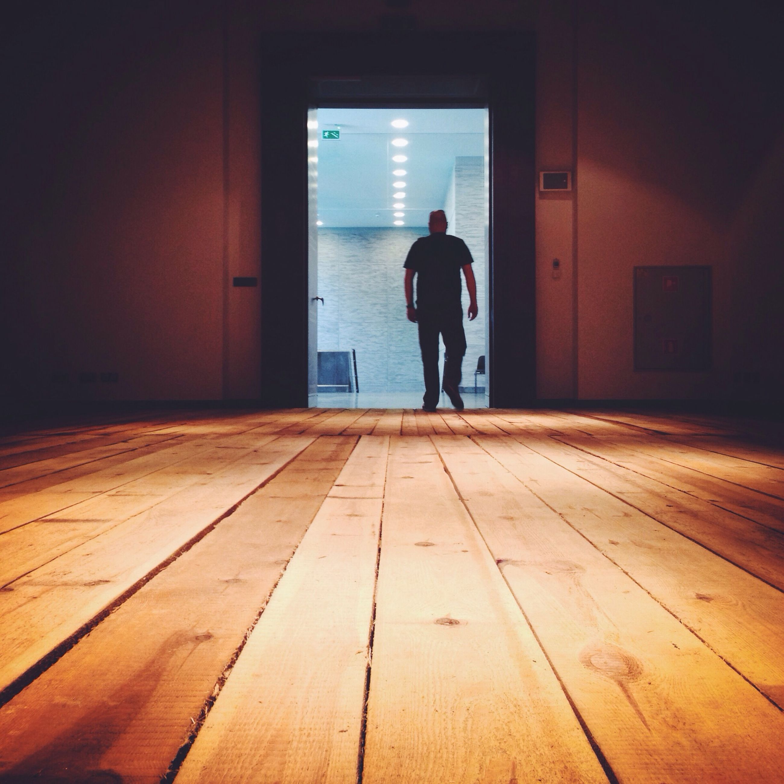 full length, indoors, lifestyles, rear view, architecture, standing, built structure, men, walking, leisure activity, silhouette, door, casual clothing, flooring, wall - building feature, corridor, person, one man only
