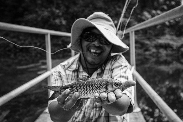 Portrait of smiling man holding fish