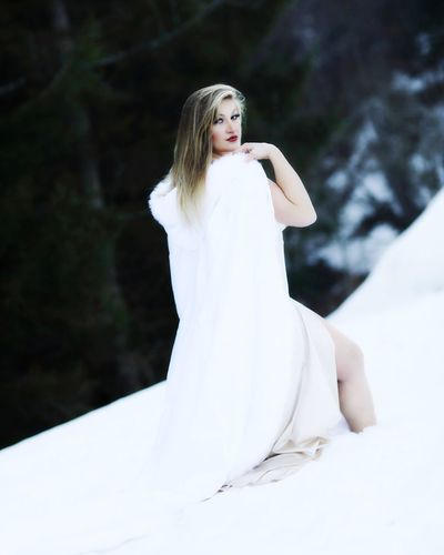 Portrait of beautiful woman wearing scarf while standing snow covered hill
