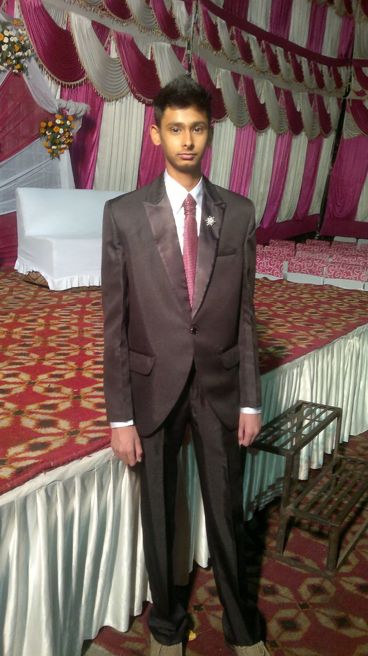 young adult, front view, looking at camera, standing, young men, suit, portrait, well-dressed, one person, businessman, one young man only, full length, formalwear, business, corporate business, lifestyles, indoors, men, real people, one man only, young women, day, only men, adults only, adult, people