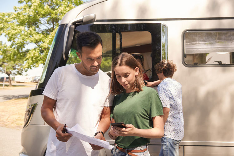 Young couple holding mobile phone while standing on bus