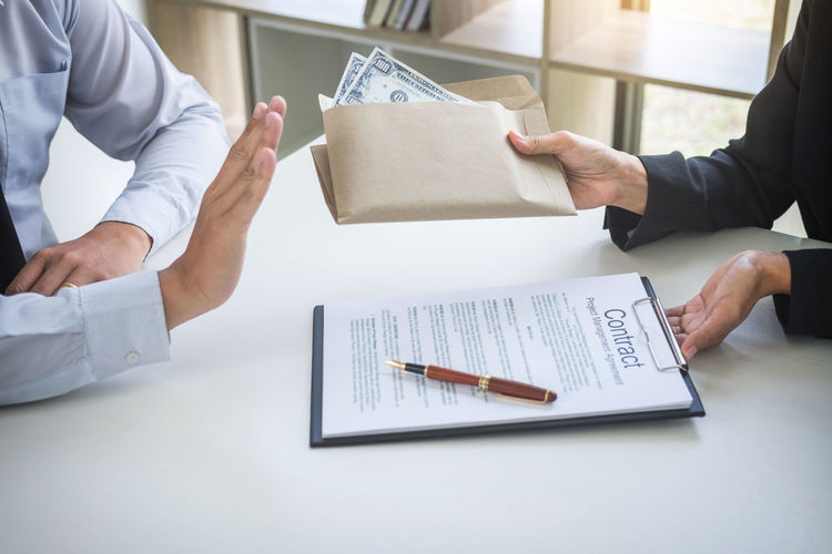 Midsection of businessman refusing bribe while colleague holding contract at desk