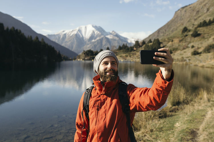 Portrait of man photographing with mobile phone standing on mountain