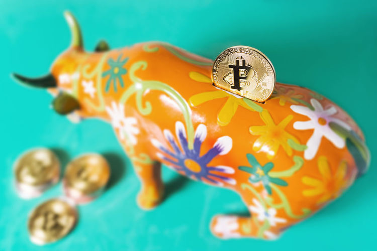 Close-up of bitcoin in piggy bank against blue background
