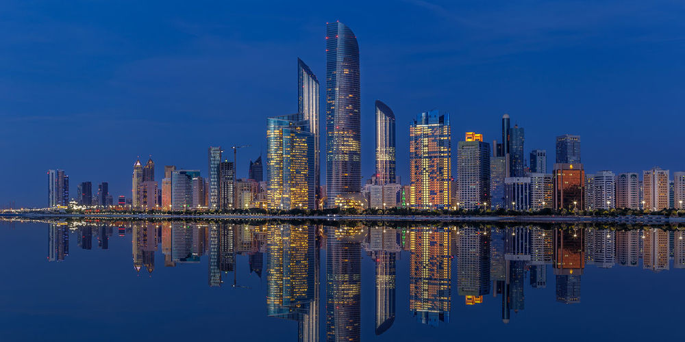 Reflection of illuminated buildings in lake against sky