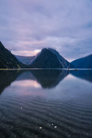 Scenic View Of Lake Against Mountains And Cloudy Sky