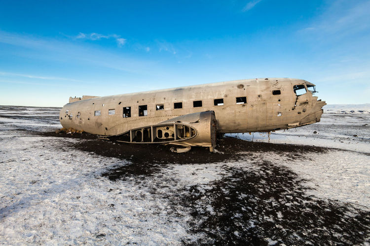 Abandoned boat on beach against sky during winter