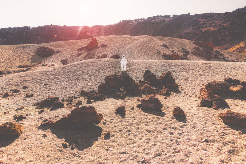 Astronaut standing on sand during sunny day