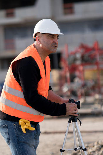 Side view of man holding camera at construction site