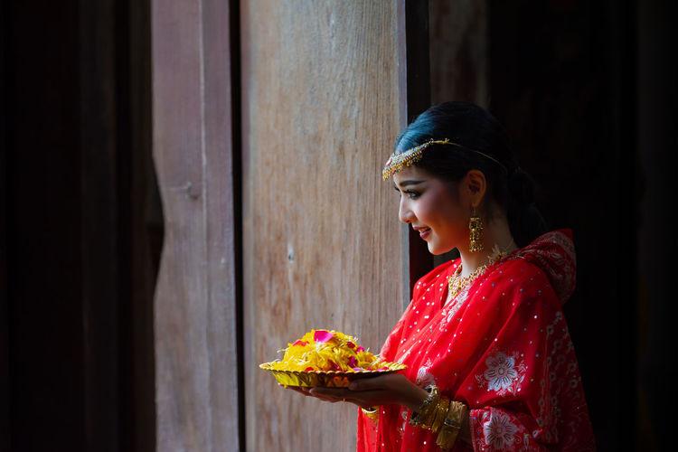 Side view of woman looking away against door