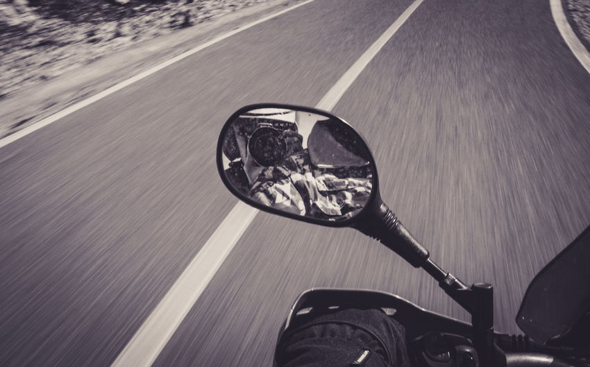 Reflection of man photographing in motorcycle mirror