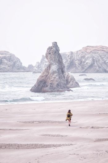Monument. Adventures with my wife on the Oregon Coast. IG @noeldxng One Person Coast Telephoto Landscape Adventure Oregon Outdoors Stark Minimalism Lone Sand Surf Full Length Sea Beach Adventure Sand Water Wave Rushing Tide Iceberg - Ice Formation Arid Landscape Be Brave A New Beginning