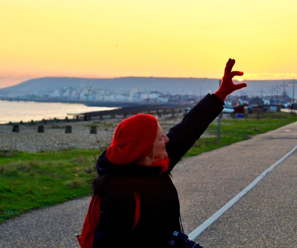 Side view of woman with hand raised standing on road against clear sky during sunset