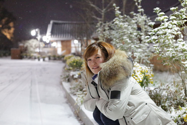 Portrait of young woman at night during winter