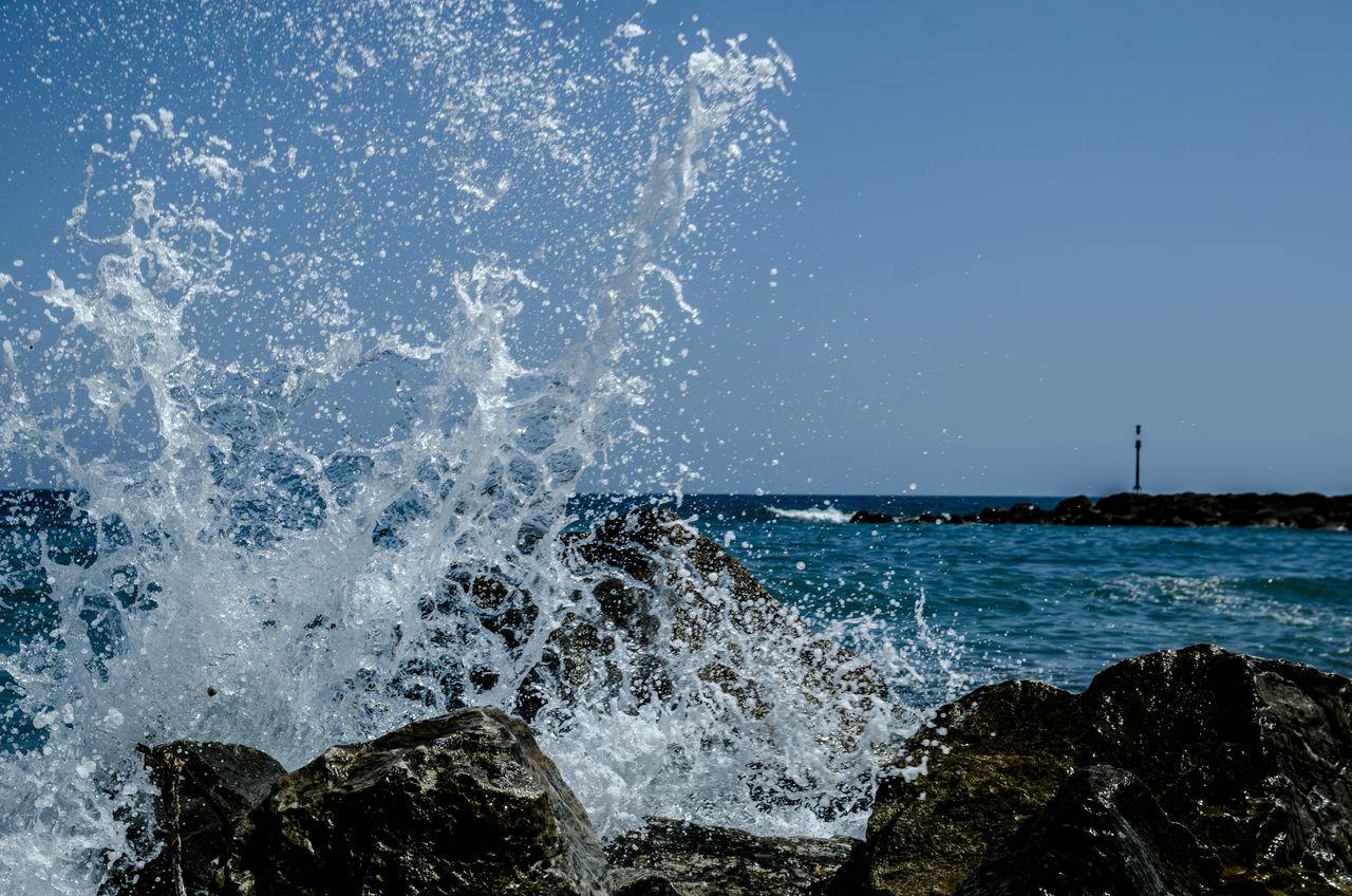 SEA WAVES SPLASHING ON ROCKS AT SHORE
