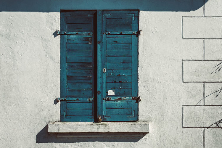 weathered shutter Shadows & Lights Architecture Blue Building Building Exterior Closed Day House Latch No People Outdoors Protection Residential District Safety Sunny Day Wall Wall - Building Feature Window Wood - Material