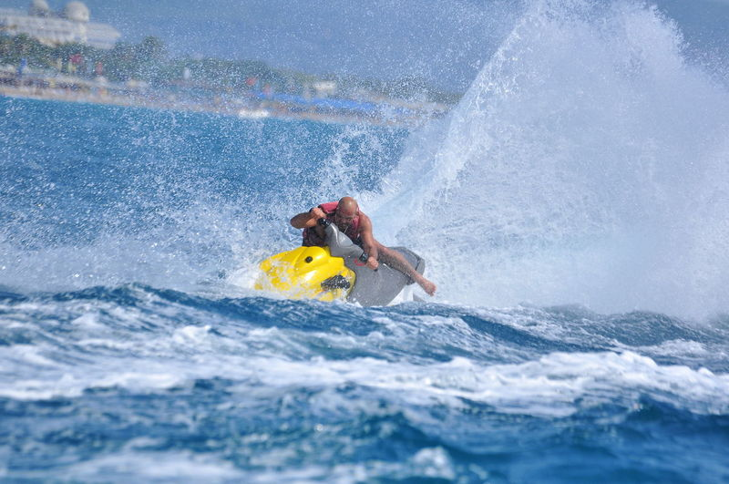 Full length of man riding jet boat in sea