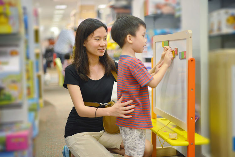 Mother Assisting Son In Sticking Number On Whiteboard