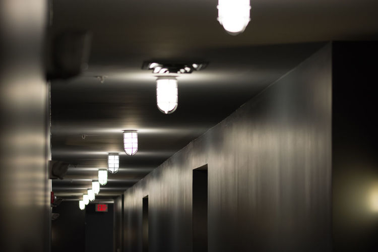 A desolate apartment building's hallway illuminated by bright lights. Absence Apartment Buildings Architecture Artificial Light Ceiling Ceiling Lights Desolate Emergency Exit Empty Places Glowing Hallway Hallway Lights Indoors  Interior Design Lightsandshadows Long Hallway Night Nightlight Noise Nikon D7200 Nikonphotography Perspective Photographyisthemuse Walls