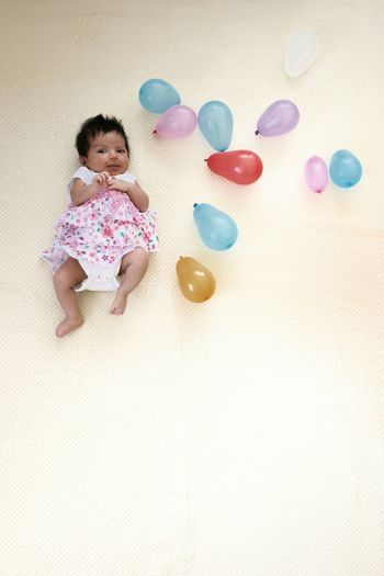 Portrait Of Cute Baby Girl With Balloons Lying On Bed