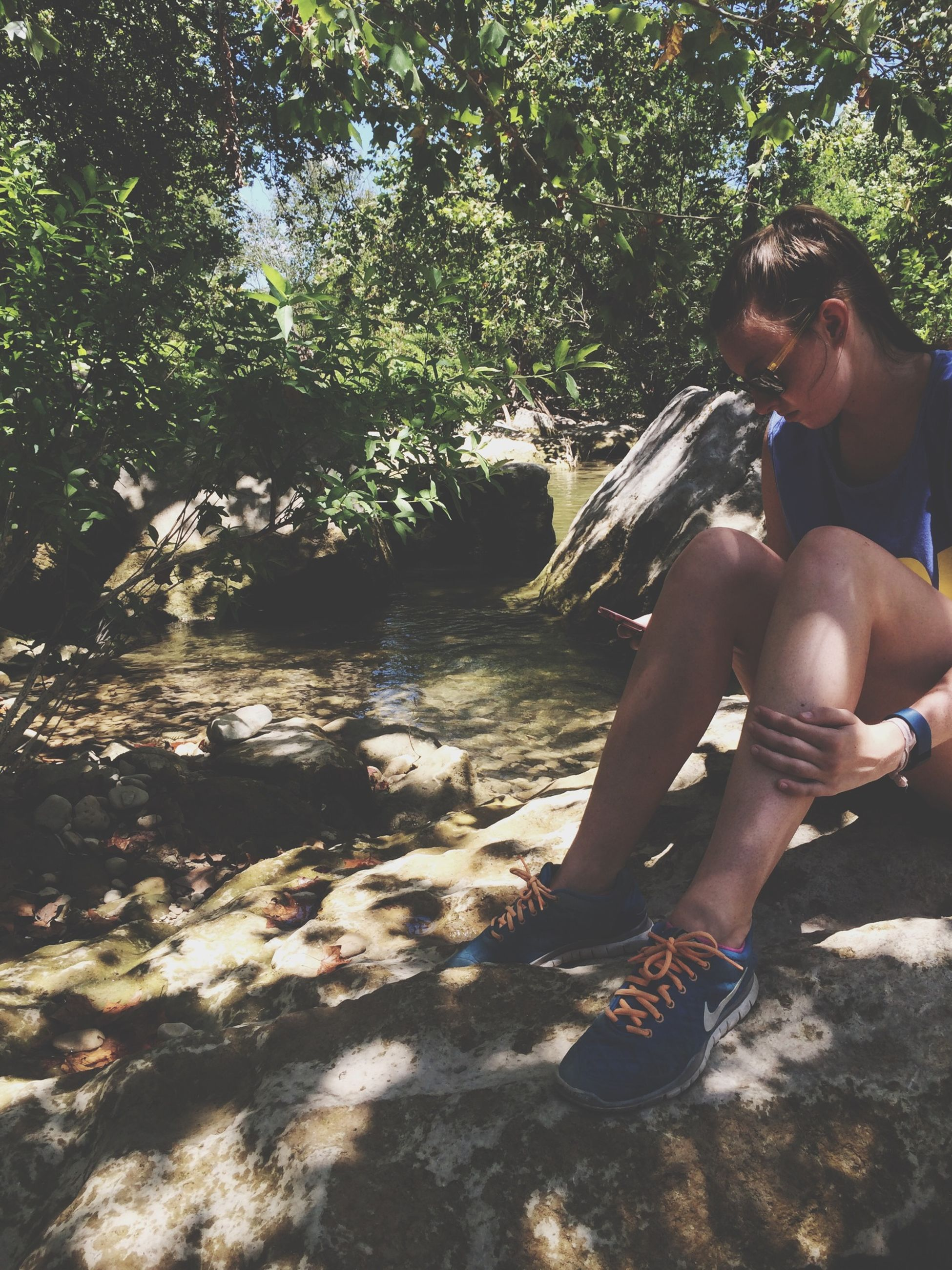 lifestyles, leisure activity, water, person, tree, young adult, casual clothing, full length, sunlight, nature, childhood, young women, day, outdoors, rock - object, standing, beach, sitting