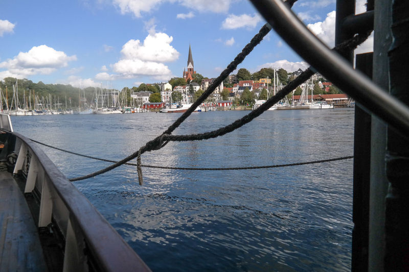 seeing the Flensburg cityscape over water through ship ropes Flensburg Water Sea Baltic Sea Flensburger Förde Transportation Mode Of Transportation Waterfront No People Railling Building Exterior Nautical Vessel Sky City Cloud - Sky Nature Day Building Railing Connection Bridge Outdoors Cityscape Passenger Craft Ropes