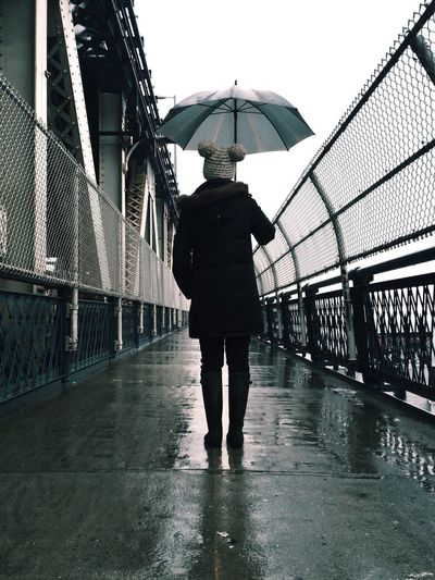 Young woman with umbrella standing on bridge