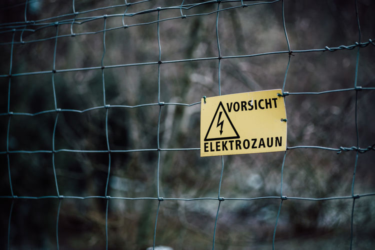 Sign Communication Text Safety Warning Sign Western Script Protection Security Focus On Foreground Fence Information Barrier Boundary Yellow Information Sign No People Metal Forbidden Non-western Script Day Outdoors Warning Symbol Aggression