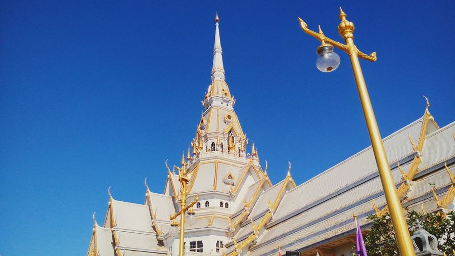 Low angle view of thai temple against clear blue sky