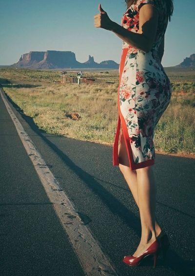 Midsection Of Woman Standing On Road Against Clear Sky