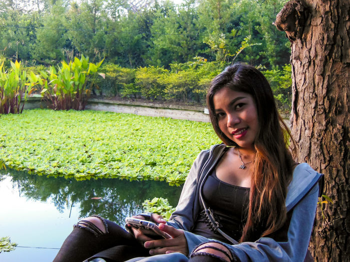 Beautiful young woman using mobile phone while sitting in park
