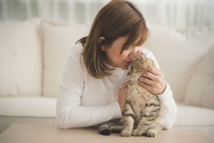 Mature Woman Kissing Cute Cat Sitting On Table At Home