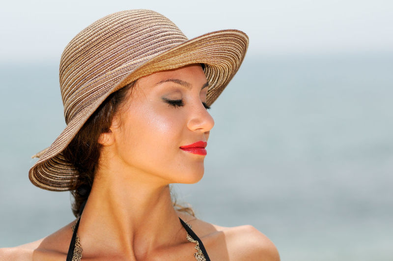 Close up portrait of a woman with a beautiful hat on a tropical beach Adult Beautiful Woman Beauty Closed Eyes Clothing Contemplation Day Focus On Foreground Hairstyle Hat Headshot Leisure Activity Lifestyles Looking One Person Outdoors Portrait Real People Sea Sun Hat Water Women Young Adult Young Women
