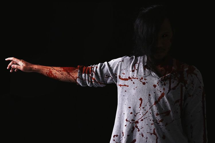 Portrait of man with arm outstretched in zombie costume standing against black background