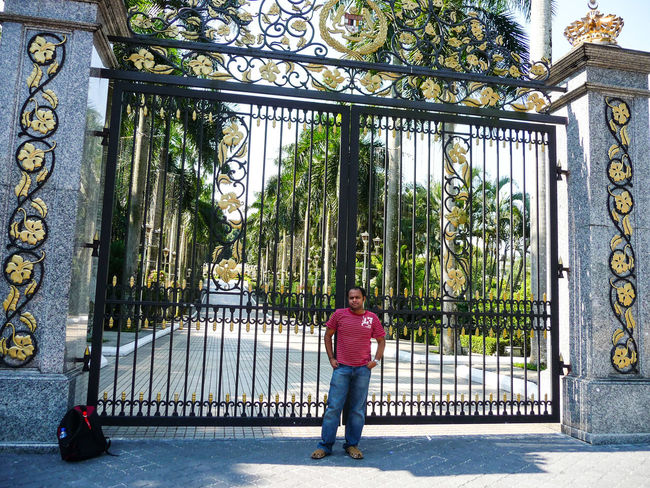 MAN IN FRONT OF GATE Full Length Men Tree Architecture Built Structure Gate Entryway City Gate Locked Entry Entrance Front Door Doorway