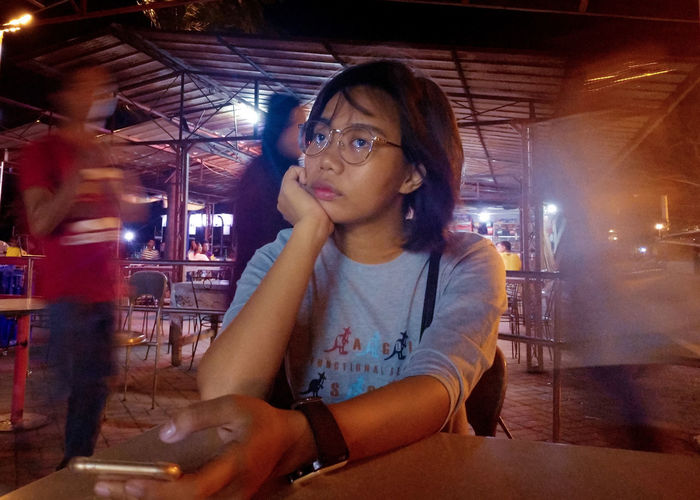Portrait of young woman sitting on table in restaurant at night